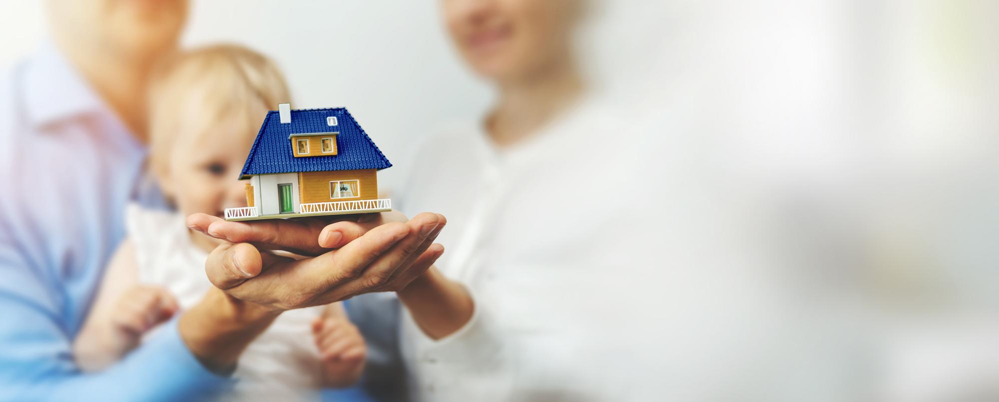 Familie hält Miniaturhaus auf Händen